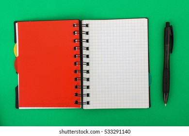 Notebook with Pen on green background. Open a blank white notebook