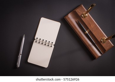Notebook with pen on a leather table