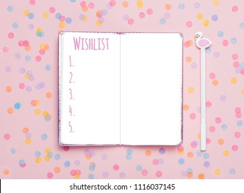 Notebook and pen on pink confetti background. Study arrangement, making wish list or plans. Flat lay, top view. Blogger's still life.