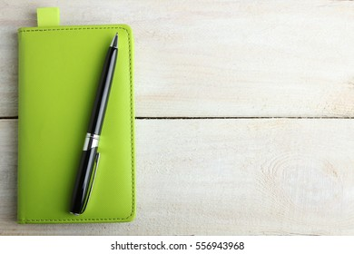 Notebook, pen on a wooden background in color green