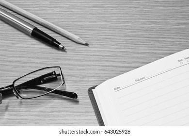 Notebook, Pen, Pencil and Glasses  on the Table