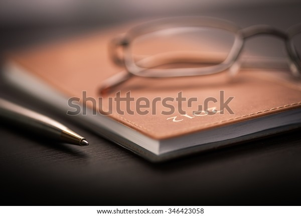 A notebook, a pen and some glasses