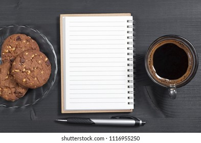 Notebook, pen, transparent cup of coffee and chocolate chip cookies with nuts on a black wooden table background, top view
