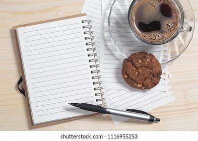 Notebook, pen and transparent cup of coffee with chocolate chip cookie on light wooden desk, top view
