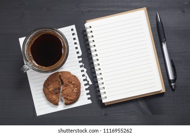 Notebook, pen and transparent cup of coffee with chocolate chip cookie with nuts on black wooden desk, top view
