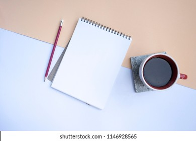The notebook with pencil and coffee was placed on a white background with cream color.