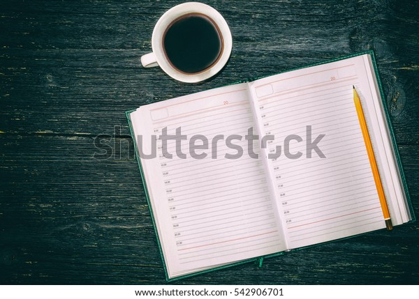 Notebook, pencil and cup of coffee on the table. Toned.