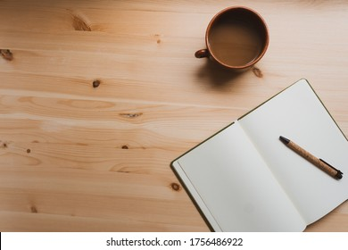 Notebook, pencil and a cup of melted chocolate in the workspace. Natural pine table. Free space on the left.
