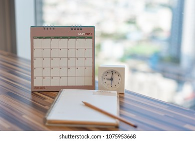 Notebook with pencil diary clock on table with May 2018 calendar at office work place. Blurred Background, Planning scheduling agenda Event organizer writing detail of plan for 2018. Calendar concept.