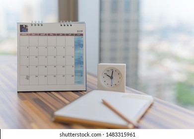 Notebook with pencil diary clock on table with September 2019 calendar at office work place with blurred background. Planning scheduling agenda Event organizer writing detail. Calendar Concept.