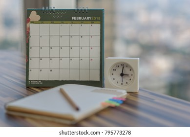 Notebook with pencil diary clock on table with February 2018 calendar at modern office. Planning scheduling agenda, Event, organizer appointment writing detail of plan for 2018. Calendar concept.