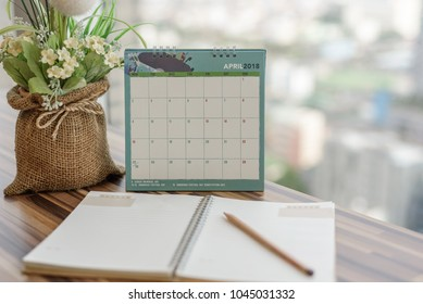 Notebook with pencil diary on table with April 2018 calendar at office work place. Blurred Background, Planning scheduling agenda, Event, organizer writing detail of plan for 2018. Calendar concept.