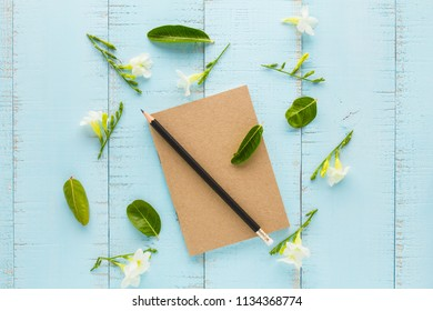 Notebook and pencil with flowers on wooden table.
