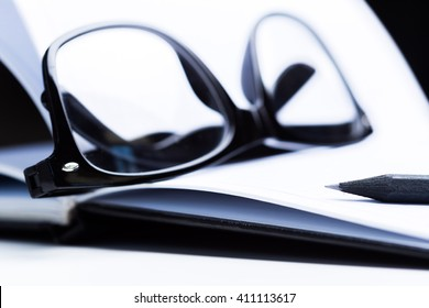 Notebook, pencil and glasses