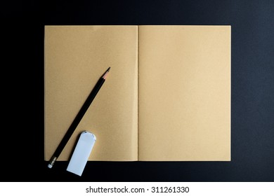 Notebook and pencil on dark background