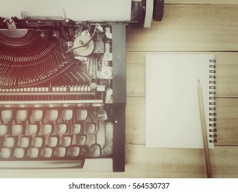 Notebook, pencil and typewriter on old wood table, process vintage tone