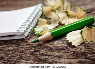 notebook with pensil and pencil shavings on wooden background