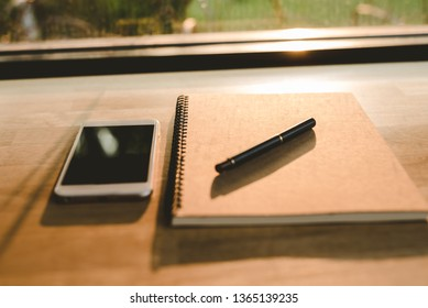 The notebook and phone and pen placed on the  table at sunset. - Image
