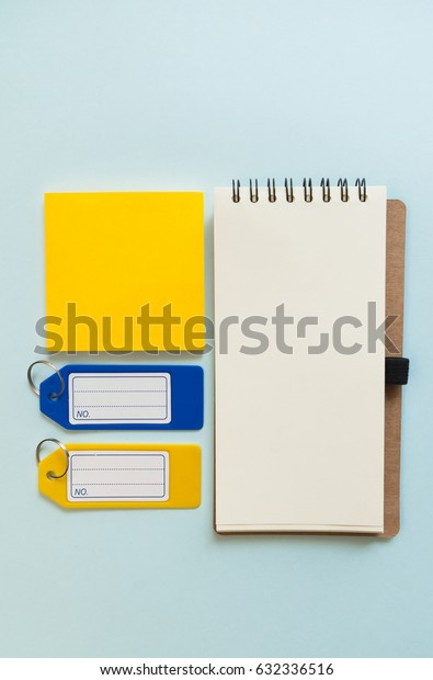 Notebook place on blue background with yellow post it, and plastic tags