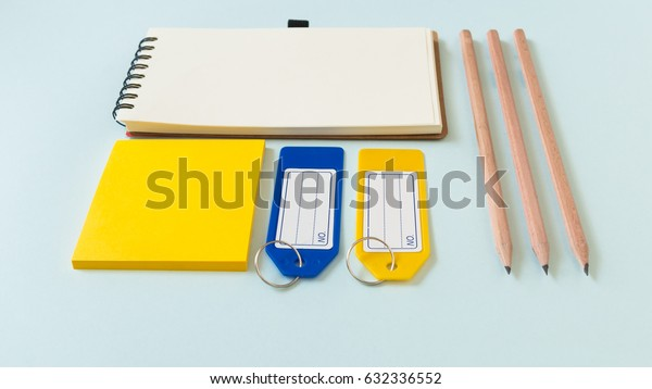 Notebook place on blue background with yellow post it, pencils and plastic tags