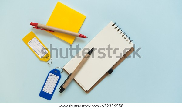Notebook place on blue background with yellow post it, pens and plastic tags