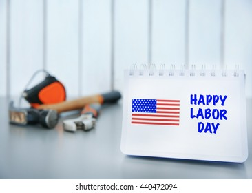 Notebook with printed text HAPPY LABOR DAY on grey table closeup