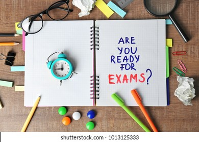 "Notebook with question ""Are you ready for exams?"" and alarm clock on table"
