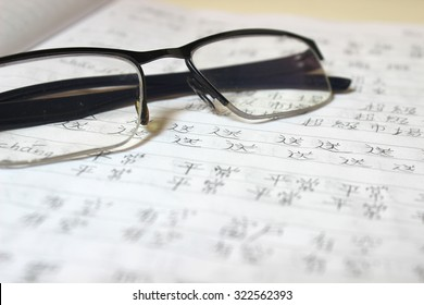 A notebook with a reading glasses and handwritten Chinese characters - Study and learn Mandarin / Chinese language