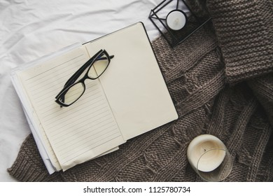 Notebook, reading glasses, pen on a blanket on a bed. Flat lay. Top view