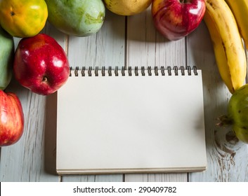 notebook for recipes with fresh fruits on wooden background