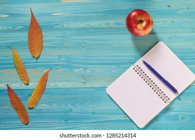 Notebook for records and autumn leaves on a wooden table. Lyrical mood