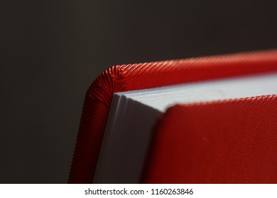 a notebook of red color in a soft cover with white sheets. close-up, macro photo. school, study, diary, notebook, book, reading