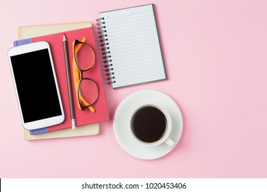 Notebook red cover mobile phone calculator and black coffee white cup orange glasses on pink background pastel style with copyspace flatlay