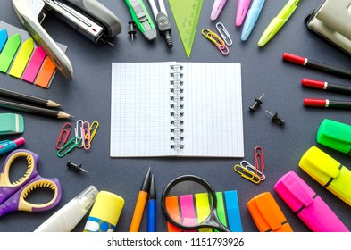 Notebook with school supplies on a black background
