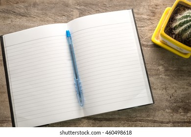 Notebook with space on the table with a pen.