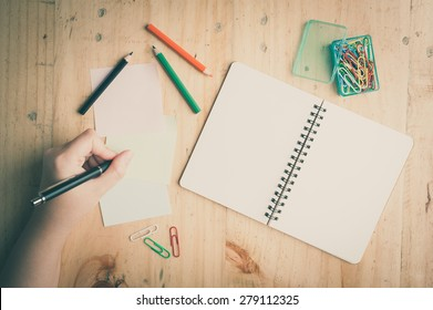 Notebook and sticky paper, paper clip, color pencil, and pen with female left hand on wood table with film filter effect