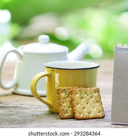 Notebook and tea with cookies on wooden table