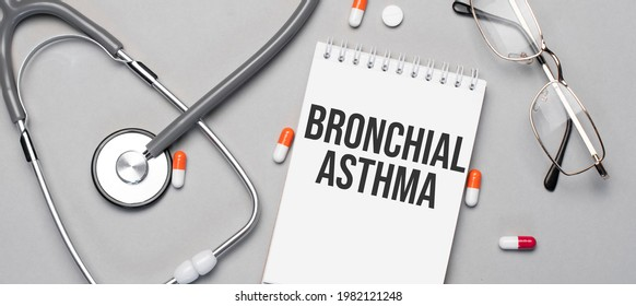 In the notebook is the text bronchial asthma, next to a stethoscope, pills and glasses.