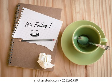 "Notebook with text "" It's Friday!"" with empty coffee cup"
