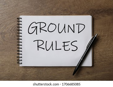 Notebook with text GROUND RULES and pen on wooden table, top view