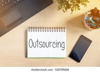 Notebook with text inside Outsourcing on table with mobile phone, laptop and plant