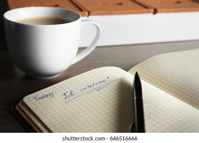 "Notebook with text ""Job interview"", pen and cup of coffee, closeup"