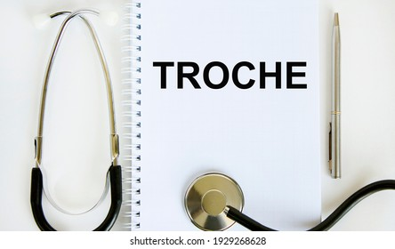 In the notebook is the text troche, next to the stethoscope and pen.