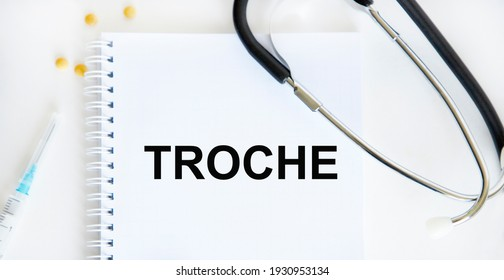 In the notebook text TROCHE, next stethoscope, syringe, tablets.