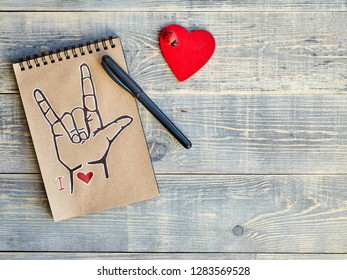 "Notebook, which is drawn ASL symbol ""I love you"" and a wooden red heart with a ladybug. All on textured boards of light blue color. There is a place for designer stickers and inserts."