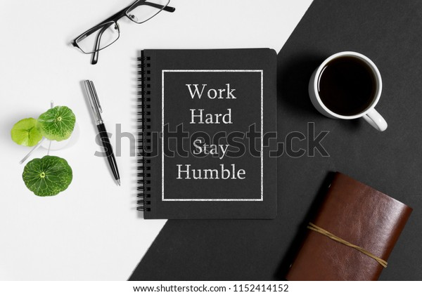 Notebook with wisdom quote and coffee cup on black and white background.