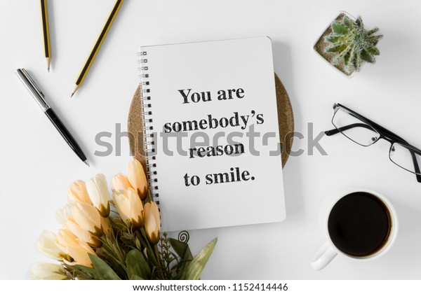 Notebook with wisdom quote and coffee cup on white background.