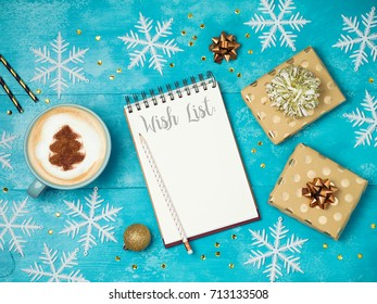 Notebook with wish list ,gift boxes and coffee cup on wooden table.Christmas holiday background. View from above. Flat lay
