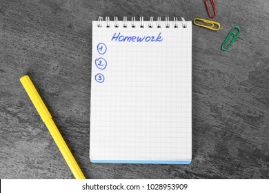 "Notebook with word ""Homework"" on table"