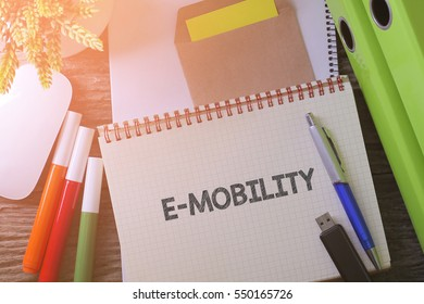 """Notebook writing """"E-MOBILITY"""" on table with Working space at the office with plant, usb drive and glasses"""